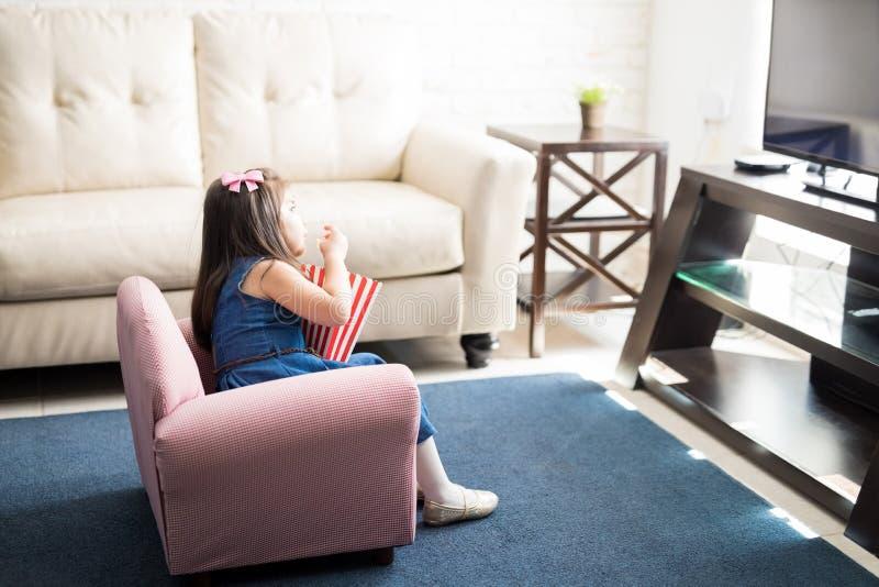 Muchacha linda que mira una película en la TV en casa imagenes de archivo