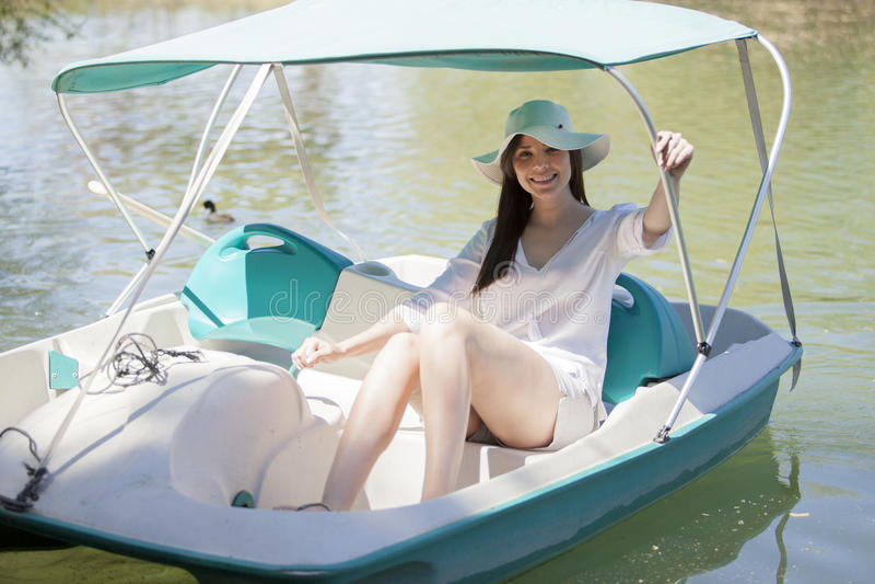 Muchacha linda que monta un barco del pedal fotos de archivo