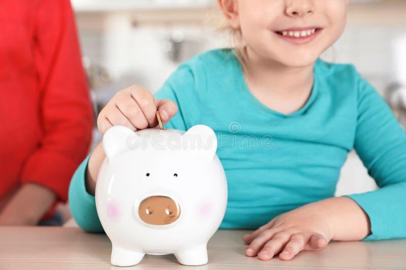Muchacha linda que pone la moneda en la hucha en la tabla Dinero del ahorro foto de archivo