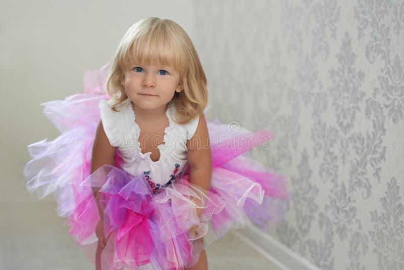 Muchacha linda que presenta en la falda rosada y violeta imágenes de archivo libres de regalías