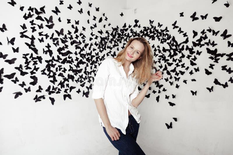 Muchacha linda que se coloca en un fondo fantástico con las porciones de mariposas fotografía de archivo libre de regalías