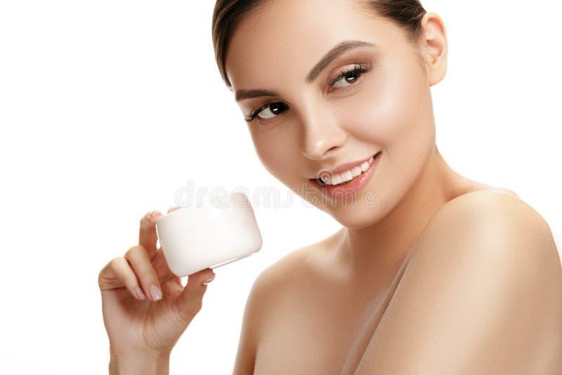 Muchacha linda que se prepara para comenzar su día Ella está aplicando la crema de la crema hidratante en cara foto de archivo