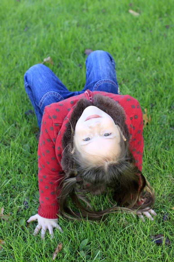 Muchacha linda que se relaja en una hierba foto de archivo libre de regalías