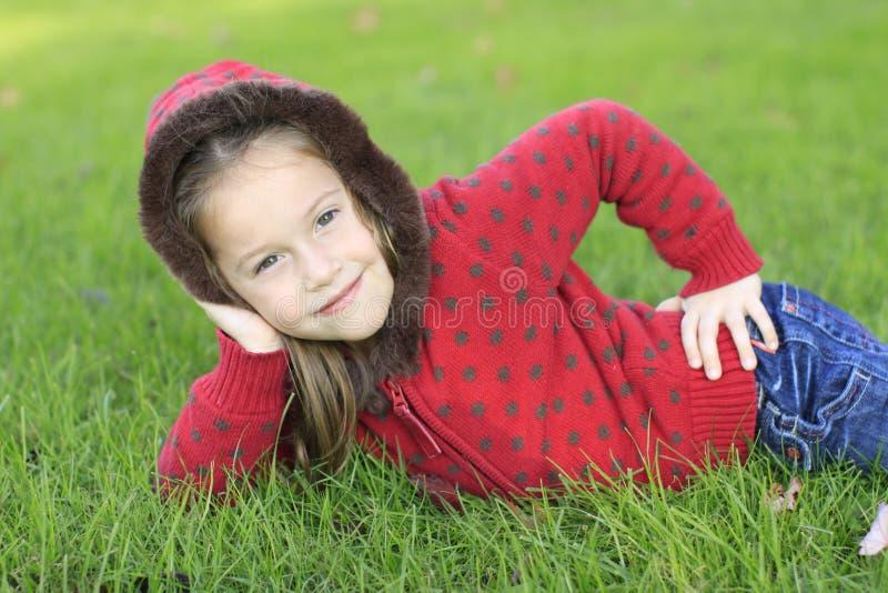 Muchacha linda que se relaja en una hierba imágenes de archivo libres de regalías