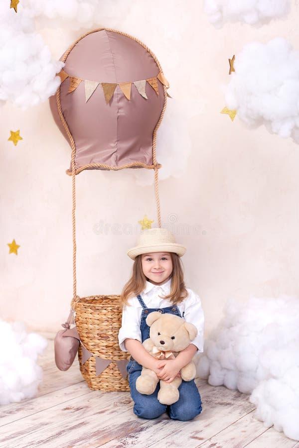 Muchacha linda que se sienta en el estudio en el fondo de un globo, de estrellas y de nubes y sosteniendo un oso de peluche La ni imágenes de archivo libres de regalías