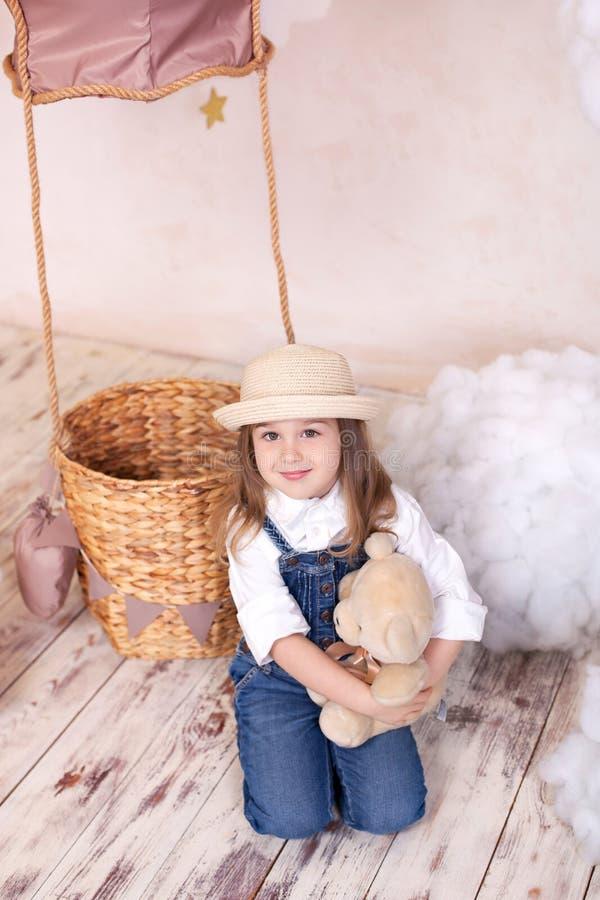 Muchacha linda que se sienta en el estudio en el fondo de un globo, de estrellas y de nubes y sosteniendo un oso de peluche La ni imagen de archivo libre de regalías