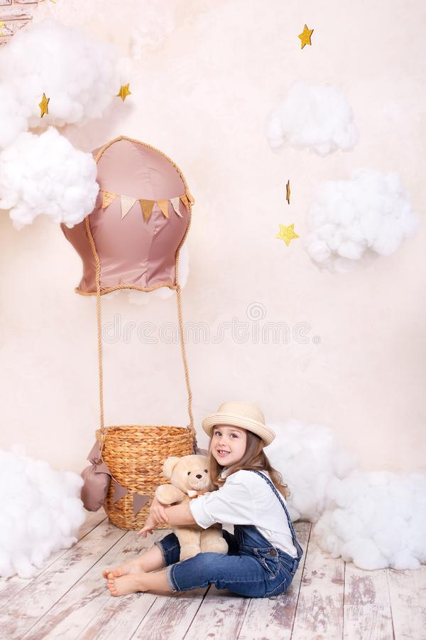 Muchacha linda que se sienta en el estudio en el fondo de un globo, de estrellas y de nubes y sosteniendo un oso de peluche La ni foto de archivo