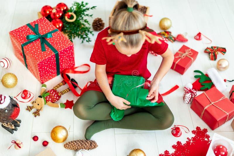 Muchacha linda que se sienta en el regalo de Navidad de apertura del piso, visión superior fotos de archivo libres de regalías