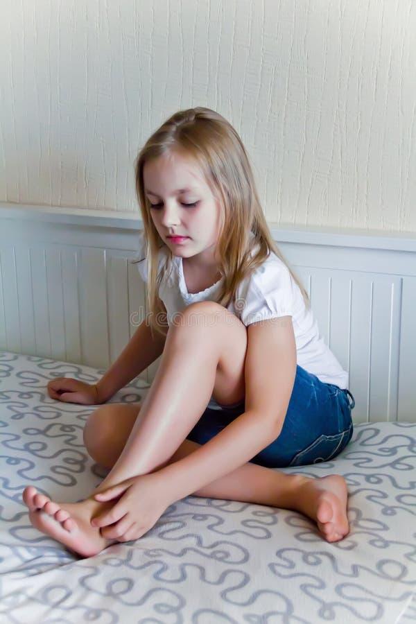 Muchacha linda que se sienta en el sofá fotos de archivo
