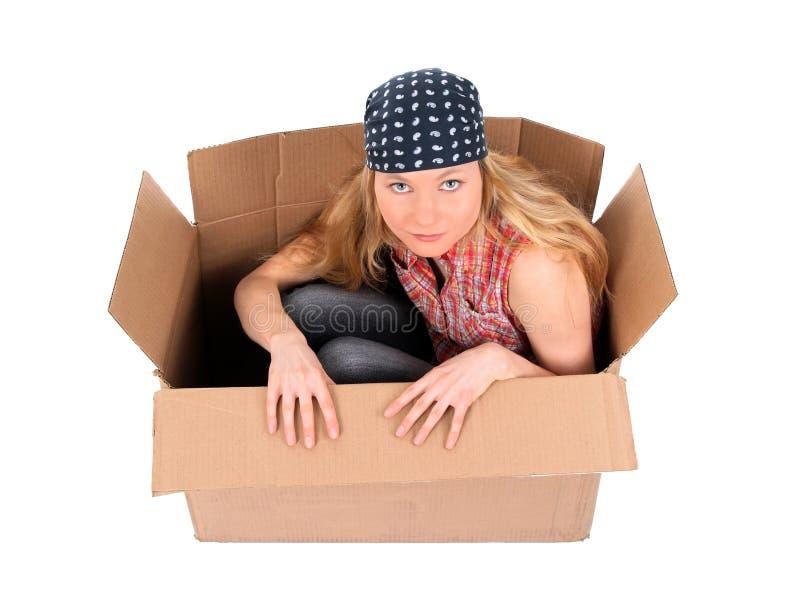 Muchacha linda que se sienta en una caja de cartón imagen de archivo libre de regalías