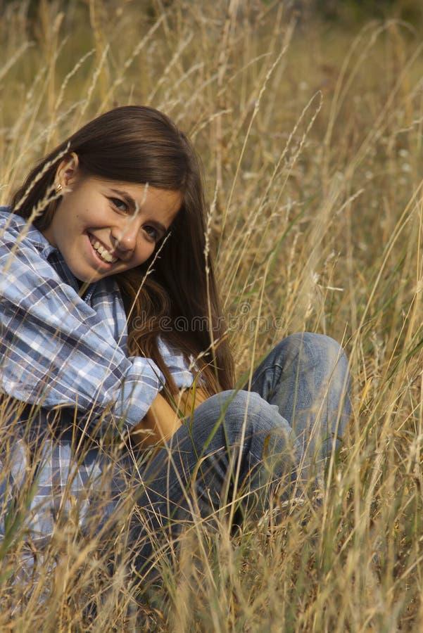 Muchacha linda que sonríe en hierba alta fotos de archivo