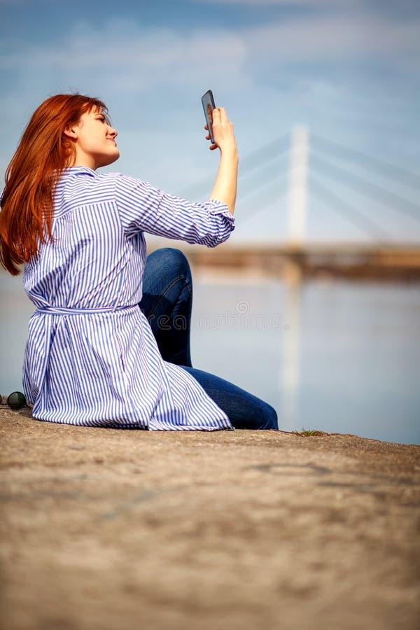 Muchacha linda que toma el selfie por el río foto de archivo