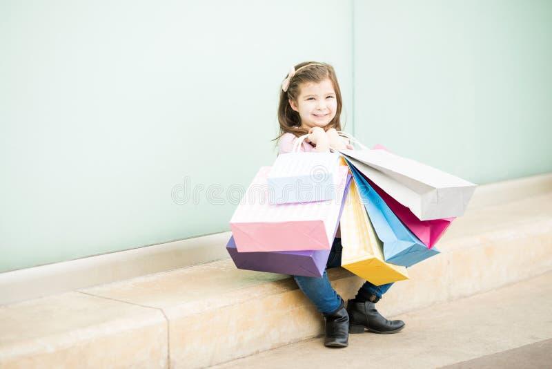 Muchacha linda que toma una rotura de hacer compras todo el día en una alameda imagen de archivo