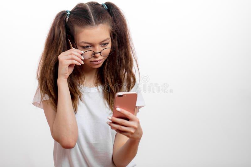 Muchacha linda seria joven que sostiene el teléfono móvil y que busca el Wi-Fi foto de archivo