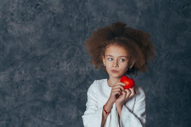 Muchacha linda sonriente con el pelo rizado que lleva a cabo un corazón rojo en sus manos imagen de archivo libre de regalías