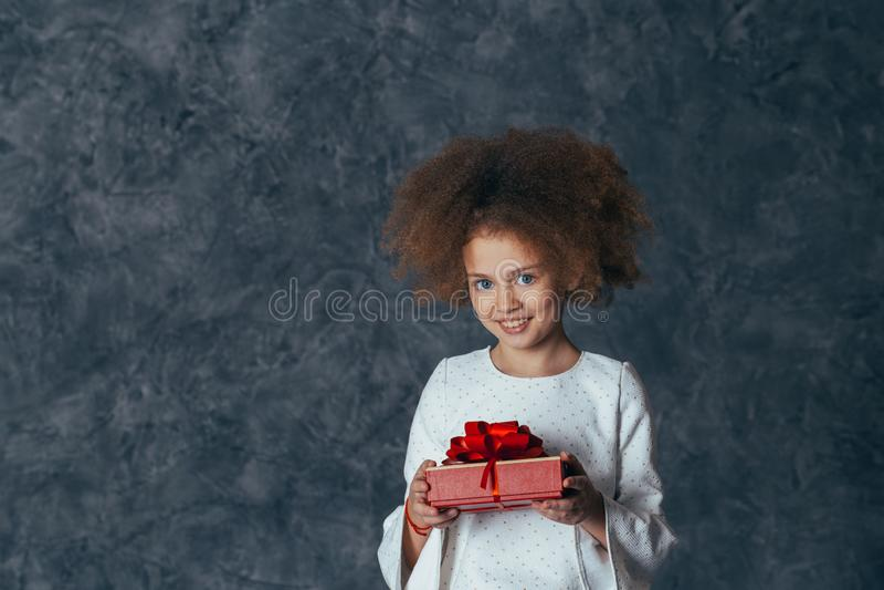 Muchacha linda sonriente con el pelo rizado que sostiene un regalo con un arco rojo fotos de archivo libres de regalías