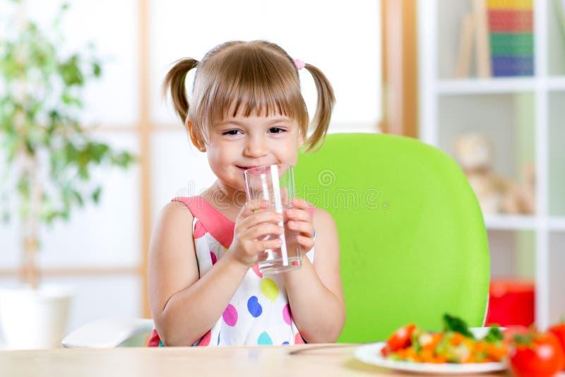 Muchacha linda sonriente que sostiene el vidrio de agua en casa fotos de archivo libres de regalías