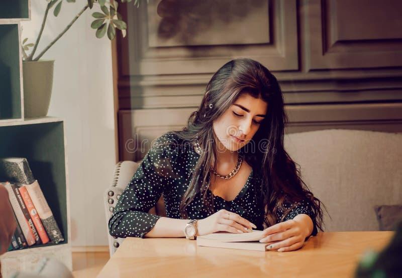Muchacha linda studing, libro del estudiante de lectura en caf? del campus, en atm?sfera rom?ntica fotos de archivo libres de regalías