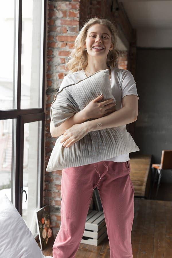 Muchacha linda vestida en el pijama que se coloca en una cama con una almohada y una sonrisa imagen de archivo libre de regalías