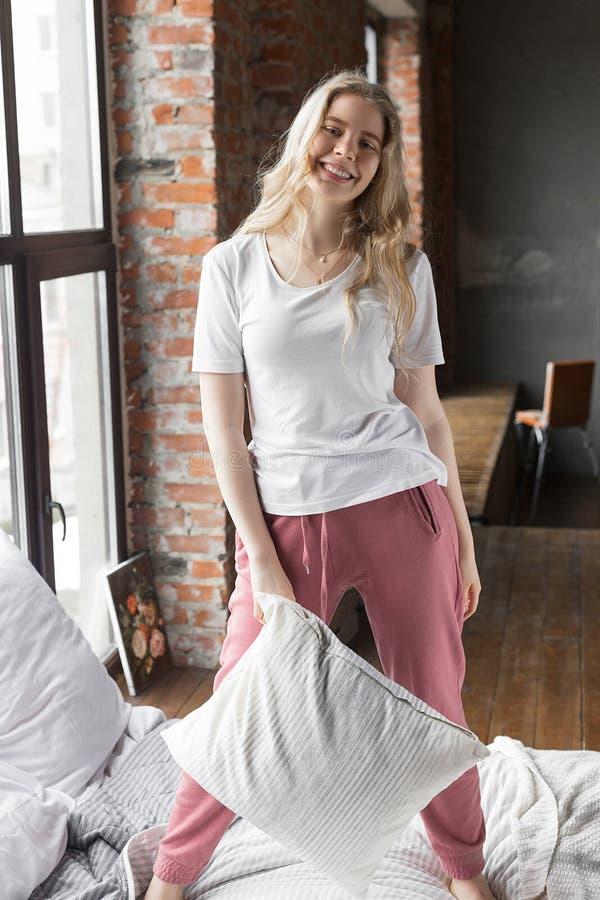Muchacha linda vestida en el pijama que se coloca en una cama con una almohada y una sonrisa foto de archivo