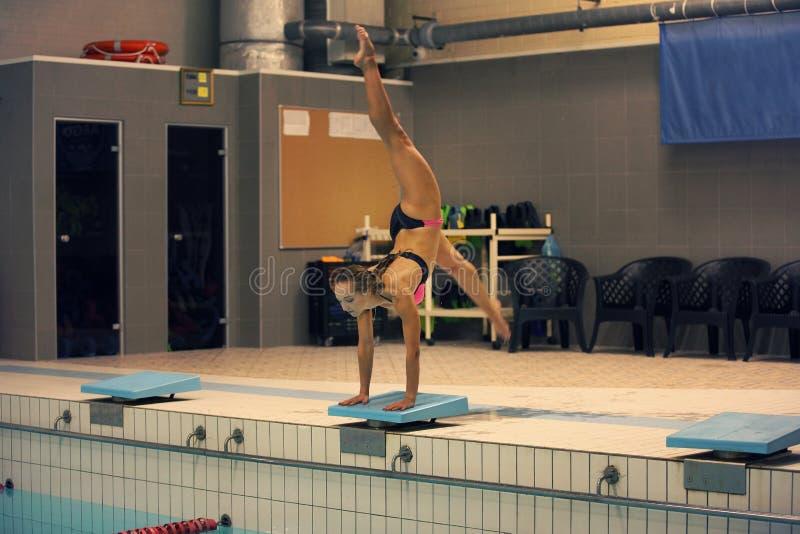 Muchacha lista para saltar en piscina del deporte interior colocación en los brazos con las piernas para arriba fotos de archivo libres de regalías