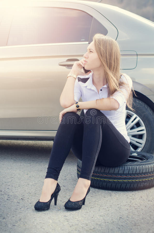 Muchacha llamada Coche quebrado en un fondo La mujer se sienta en una rueda Reparación atractiva de la mujer joven un coche Fondo imágenes de archivo libres de regalías