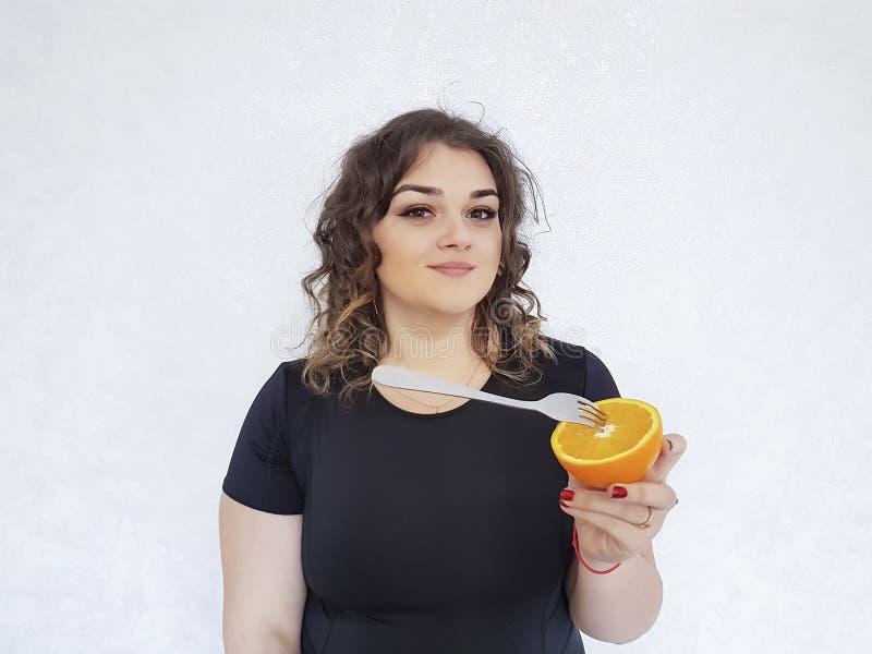 Muchacha llena hermosa con las naranjas imagenes de archivo