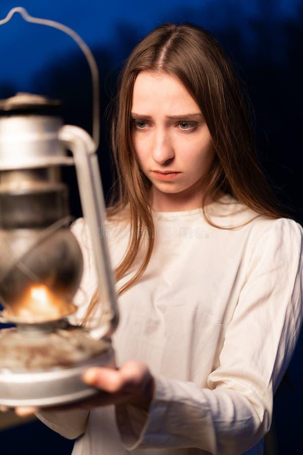 Muchacha mística misteriosa en un bosque oscuro de la noche con una lámpara de keroseno en sus manos fotografía de archivo