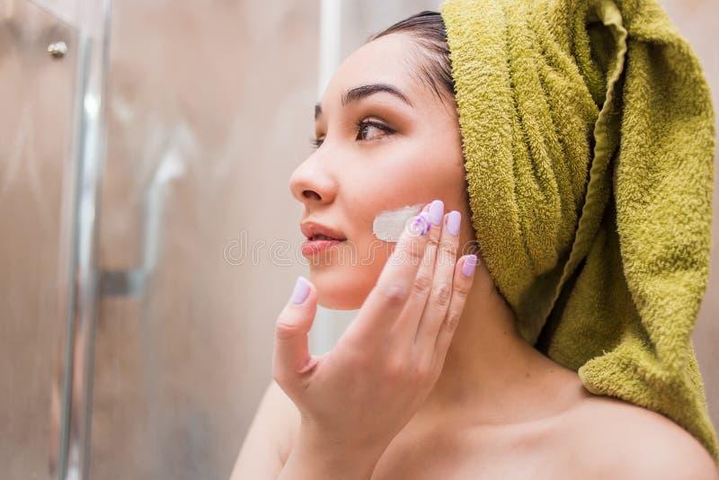 Muchacha magnífica que aplica la crema hidratante en su cara después de una ducha Cuidado de piel foto de archivo libre de regalías