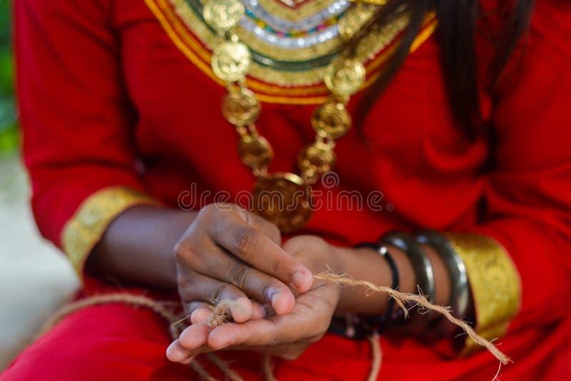 Muchacha maldiva que hace la cuerda a mano hecha a mano foto de archivo libre de regalías