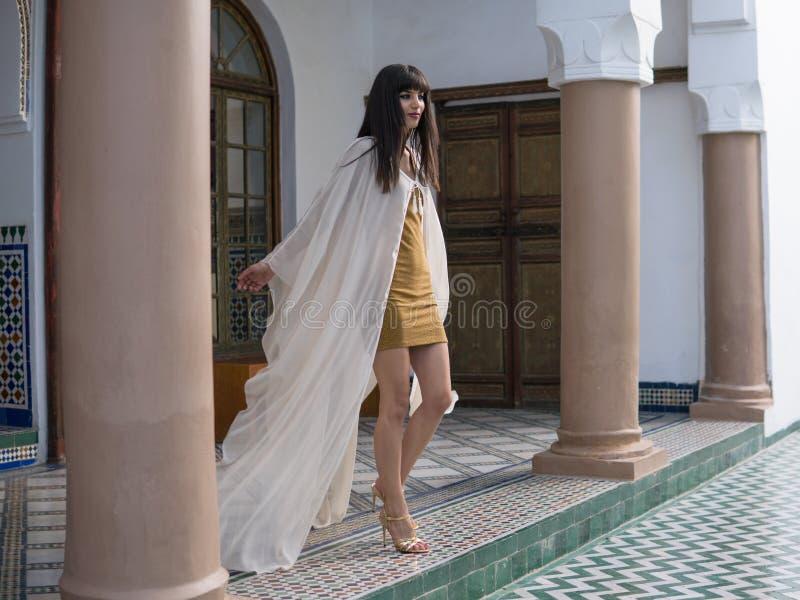 Muchacha marroqu? hermosa que agita su capa blanca en interior rico de Dar Si Said Riyad pintoresco en Marrakesh foto de archivo libre de regalías
