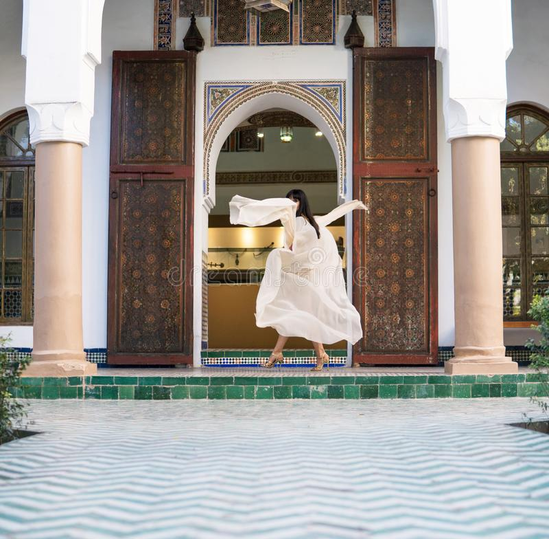 Muchacha marroqu? hermosa que agita su capa blanca en interior rico de Dar Si Said Riyad pintoresco en Marrakesh foto de archivo