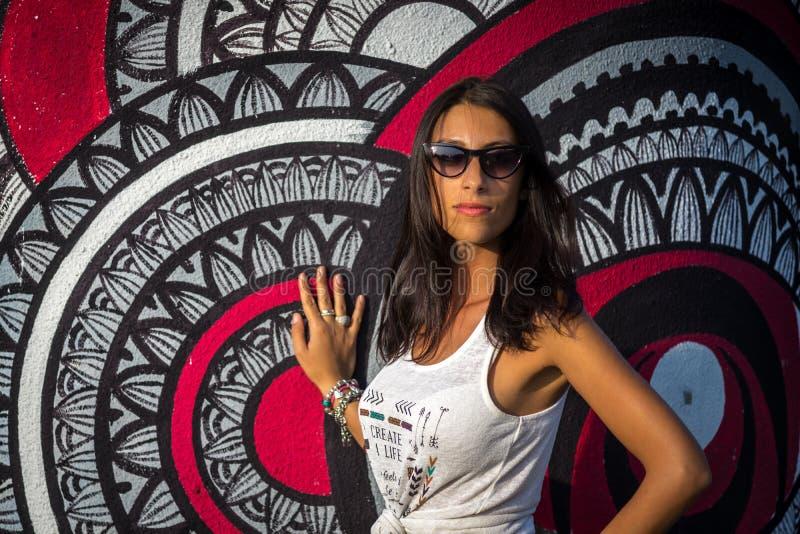 Muchacha mediterránea joven en la camiseta blanca que presenta cerca de la pared foto de archivo libre de regalías