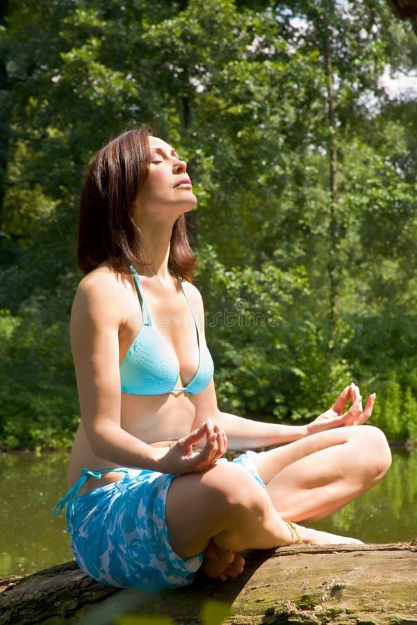 Muchacha mediteting en costa del lago de madera foto de archivo