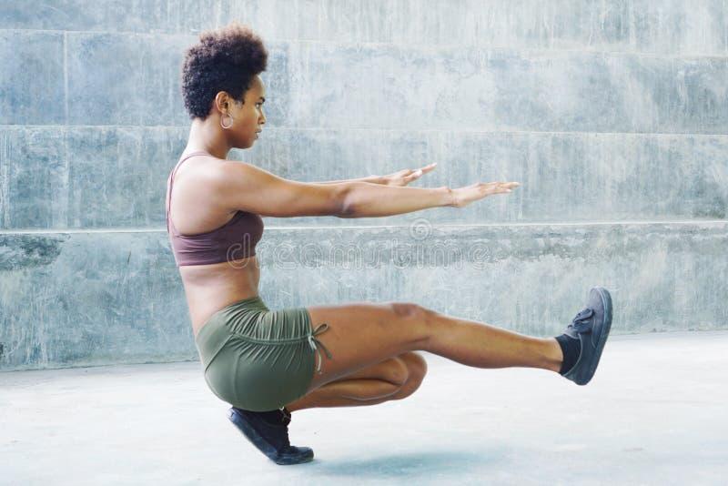Muchacha melanesia del atleta del isleño pacífico con el afro que se realiza ejercitando las rutinas que sientan el tablón fotos de archivo libres de regalías