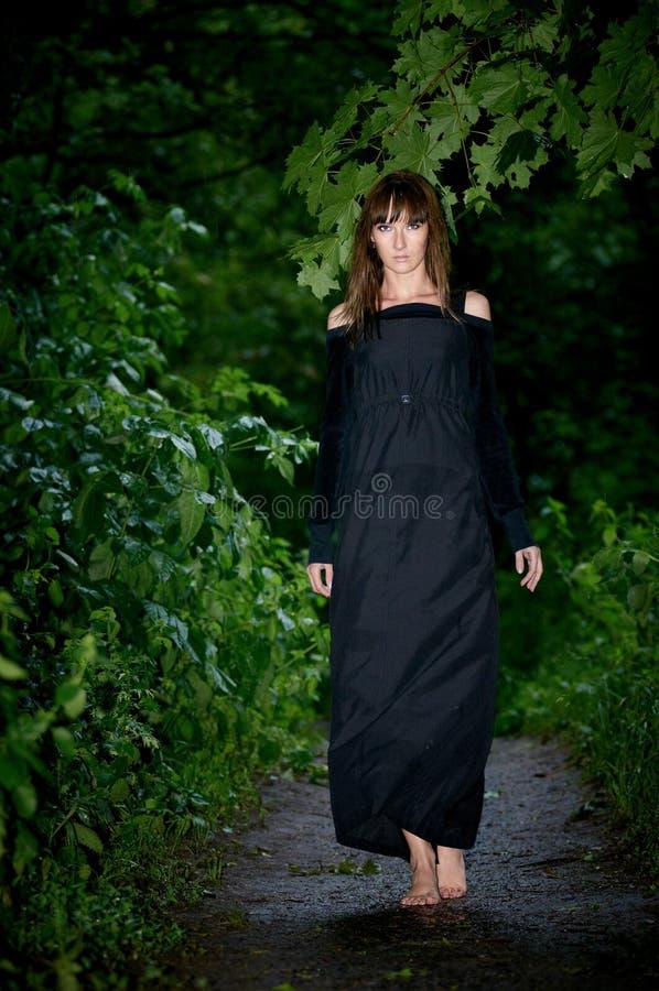 Muchacha misteriosa hermosa que camina descalzo en el bosque después de r imagen de archivo
