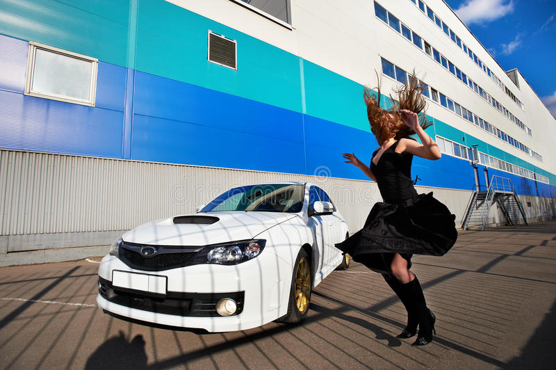 Muchacha misteriosa que salta cerca del coche blanco fotos de archivo