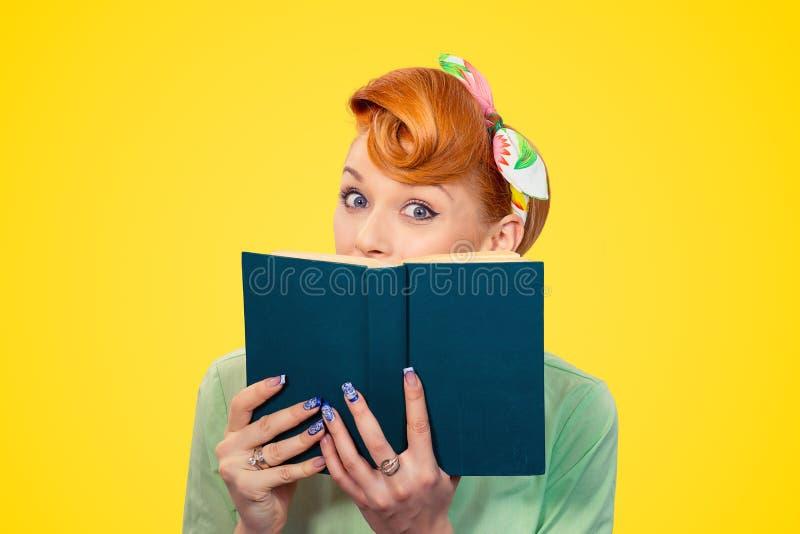 Muchacha modela chocada que se oculta detrás de un libro imagenes de archivo