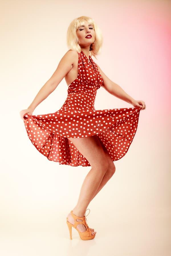 Muchacha modela en el baile retro del vestido de la peluca rubia foto de archivo