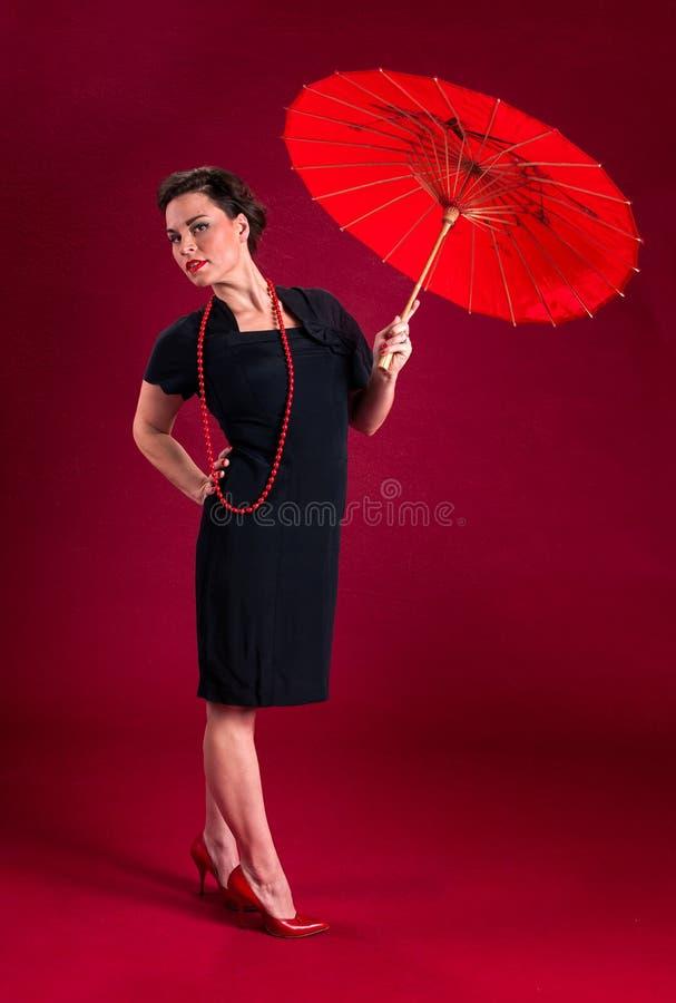 Muchacha modela en vestido negro con el parasol rojo foto de archivo libre de regalías