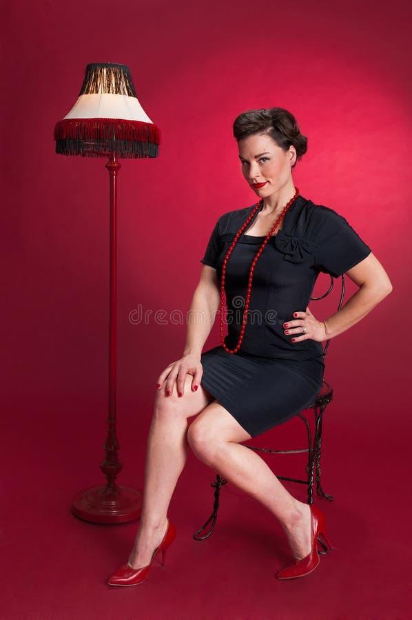 Muchacha modela en vestido negro con la lámpara foto de archivo