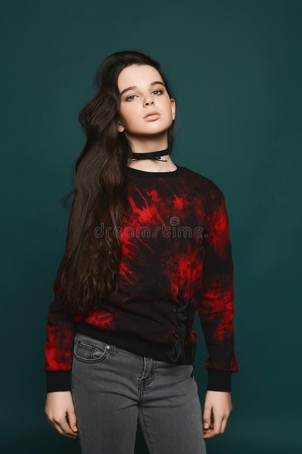 Muchacha modelo adolescente morena joven que presenta en el fondo verde oscuro imagen de archivo
