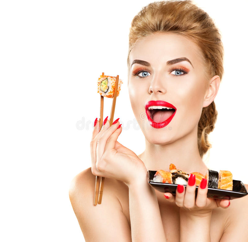 Muchacha modelo de la belleza que come los rollos de sushi imagen de archivo