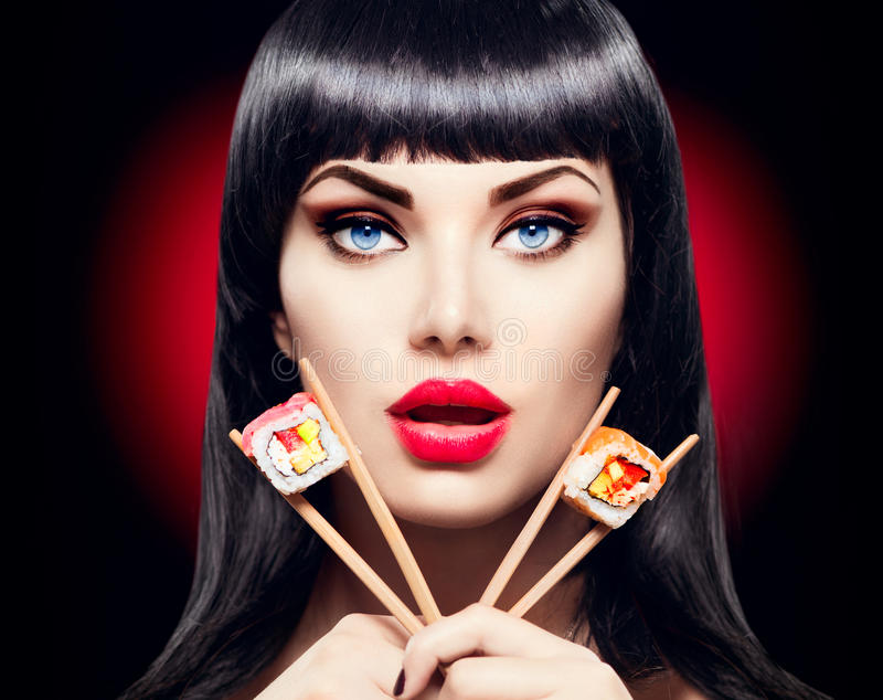 Muchacha modelo de la belleza que come los rollos de sushi foto de archivo libre de regalías