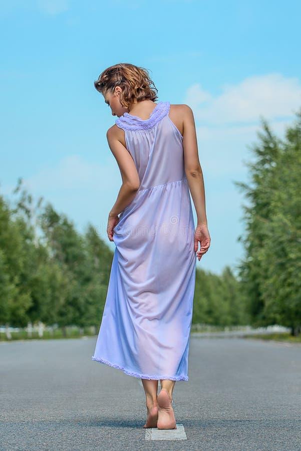 Muchacha modelo delgada hermosa en un vestido de seda púrpura de la parte posterior en el camino fotografía de archivo