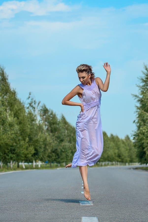 Muchacha modelo delgada hermosa en un vestido de seda púrpura que presenta suavemente en salto del baile en el camino imagenes de archivo