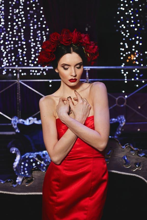 Muchacha modelo delgada morena de moda con maquillaje brillante y con una guirnalda floral roja en su cabeza en satén elegante ro imagenes de archivo