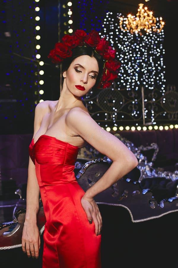 Muchacha modelo delgada morena de moda con maquillaje brillante y con una guirnalda floral roja en su cabeza en satén elegante ro foto de archivo