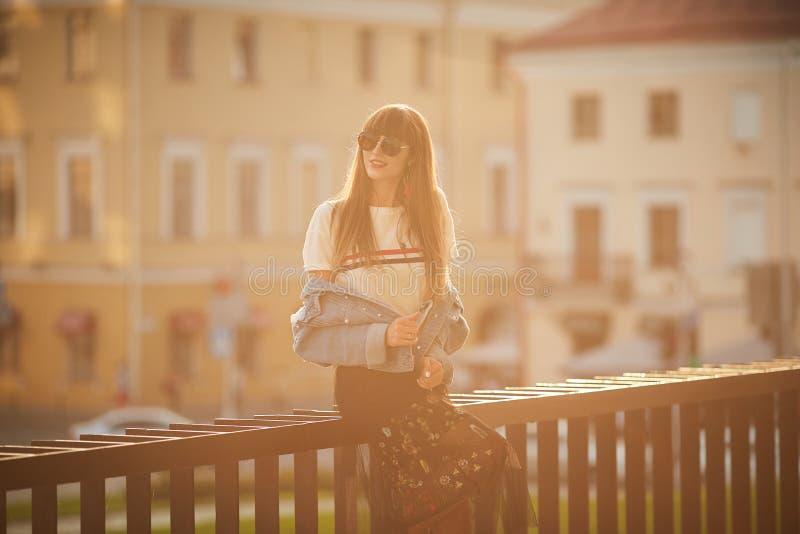 Muchacha modelo feliz y hermosa con el cuerpo perfecto en chaqueta de los vaqueros y en las sonrisas de moda de la falda y la pre fotografía de archivo