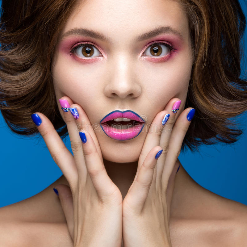 Muchacha modelo hermosa con maquillaje brillante y esmalte de uñas coloreado Cara de la belleza Clavos coloridos cortos imagen de archivo libre de regalías